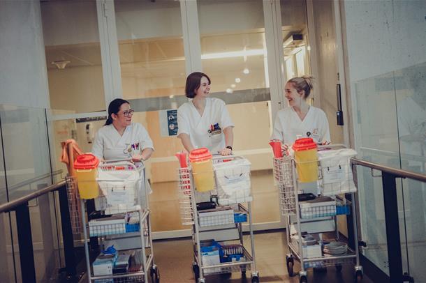 Tre bioingeniører som går med labtralle