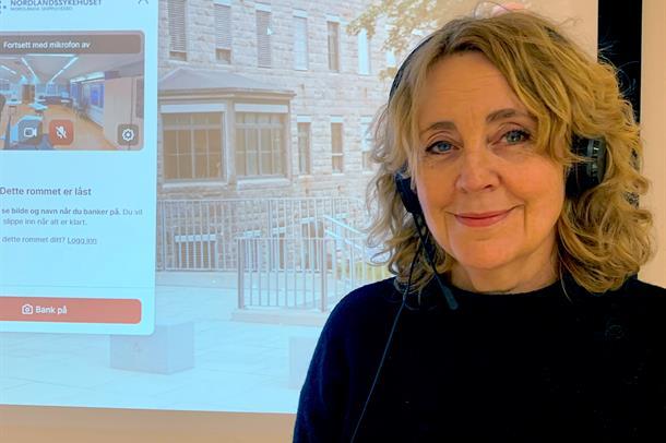 Dame med headset foran storskjerm med digitalt møterom