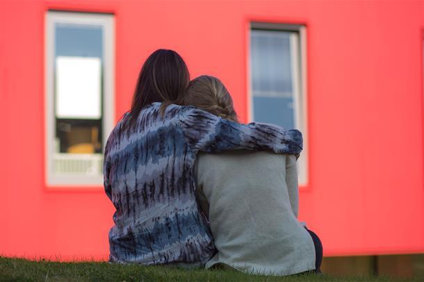 To personer som sitter på gresset med ryggen mot kamera