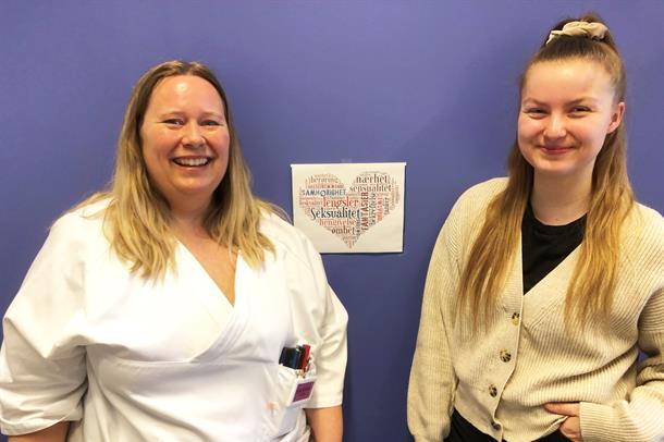 To damer som smiler foran en blå vegg