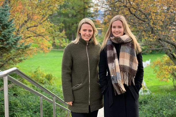 To damer som står og smiler mot kamera i høstlige omgivelser