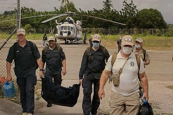 Fem menn som går fra et helikopter mot kamera